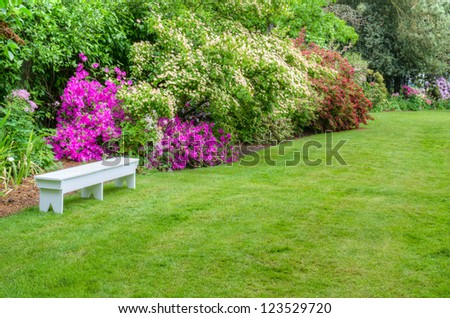 A garden scene with blooming azaleas and a white bench - stock photo