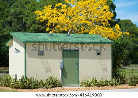 A garden shed made of concrete block and stucco exterior with a green wood roof.  A flowering Yellow Tab tree in the background along with pines in a Florida garden setting in Springtime.