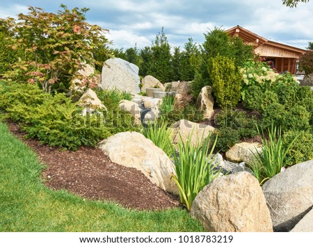 Garden large stones coniferous plants on stock photo image a garden with large stones and coniferous plants on the slope and a wooden house with workwithnaturefo