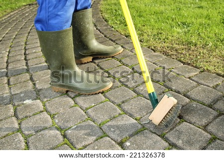 A Gardener  scratching moss out of paving stones - stock photo
