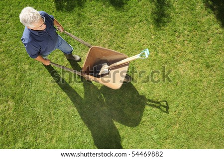 A gardener setting off to work with his wheelbarrow and tools, taken from a high viewpoint. Space for text to right and at base of image - stock photo