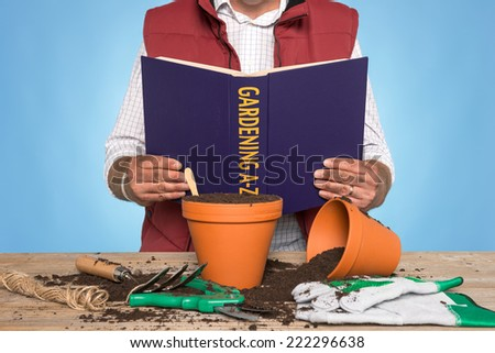 A gardener standing at a workbench reading a GARDENING A-Z book - stock photo
