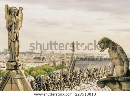 A gargoyle and an angel in Notre Dame. Vintage style photo - stock photo