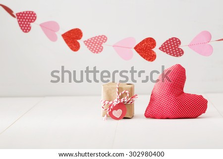 A garland of hearts above a small gift-wrapped box and red textile heart on a neutral off white background with copyspace - Valentines Day greeting card background  - stock photo