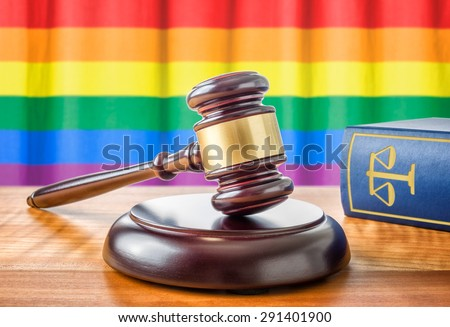 A gavel and a law book - Rainbow flag - stock photo