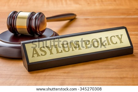 A gavel and a name plate with the engraving Asylum Policy - stock photo