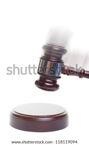 A gavel striking down on a block with motion blur added - stock photo