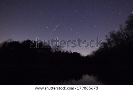 A Geminid Meteor in the night sky over Lake Norman in North Carolina - stock photo