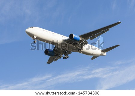 A generic airline airplane landing with undercarriage wheels and flaps down - stock photo