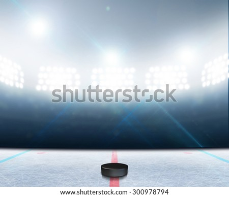 A generic ice hockey ice rink stadium with a frozen surface and a hockey puck under illuminated floodlights - stock photo