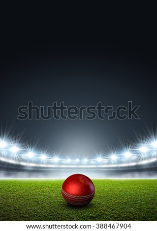 A generic stadium with an unmarked green grass pitch at night under illuminated floodlights and a red cricket ball - stock photo