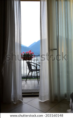 a gentle breeze wafts the curtains of a hotel room with balcony. through the open windows a romantic view of a lake in the mountains - stock photo