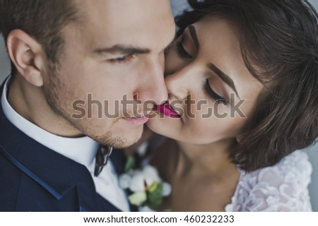 A gentle kiss of the newlyweds on the background of bright Windows.