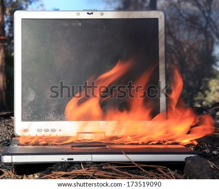 A genuine Lap Top Computer completely engulfed in flames of fire.  Computer damage due to a person typing so fast they burned up the internet or were writing something so HOT it literally caught fire - stock photo