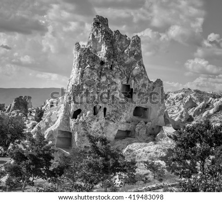 A geological formation consisting of volcanic tuff with cave dwelling. Cappadocia in Central Anatolia is a UNESCO World Heritage Site since 1985, Turkey (black and white) - stock photo