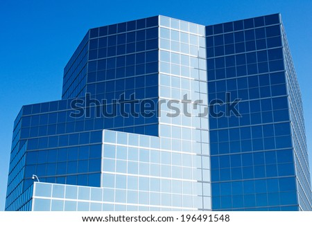 A geometric building made of glass panes under a blue sky.
