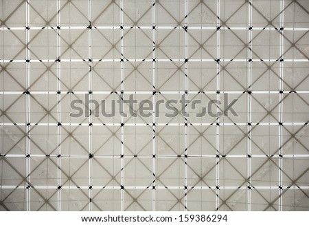 A geometric pattern of fabric squares is supported by a lattice structure of beams overhead in a museum. The cloth is dirty in sections. - stock photo
