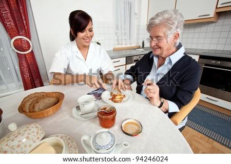 a geriatric nurse helps elderly woman at breakfast - stock photo