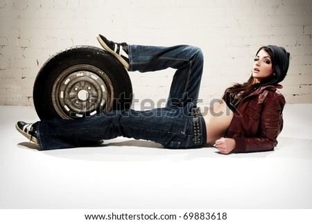 A ghetto styled girl posing in front of brick wall with a wheel