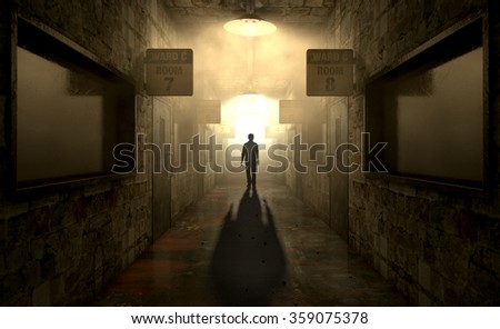 A ghostly figure casts a long shadow down the middle of a dimly lit passage of a dilapidated mental asylum  - stock photo
