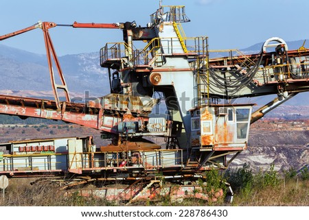 A giant Bucket Wheel Excavator at work in a lignite pit mine with a dirt road leading to it in the foreground. Close up - stock photo
