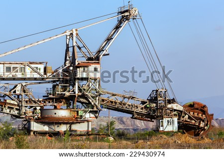 A giant Bucket Wheel Excavator at work in a lignite pit mine with a dirt road leading to it in the foreground - stock photo