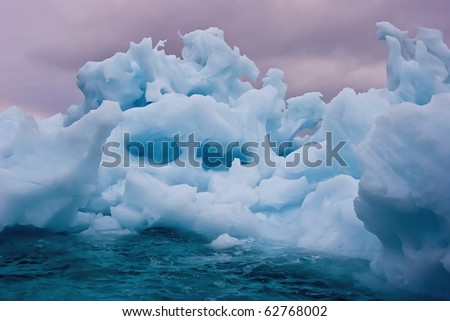 a giant iceberg floating under a stormy sky at sunrise, greenland - stock photo