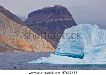 a giant iceberg floats on the sea in greenland - stock photo