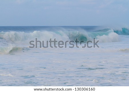 A giant wave breaking during a storm on the north shore of Oahu in Hawaii. These incredible waves have tons of white water and froth with hollow barrels and a dangerous rip current. - stock photo