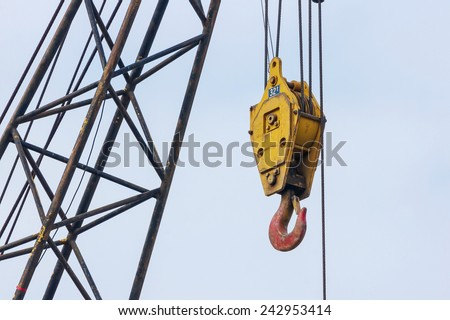 A Giant Yellow Hook Beside The Steel Struts As Part of A Tower Crane. Aged And Weathered. - stock photo