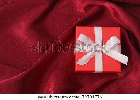 a gift box on a red satin background, from above - stock photo