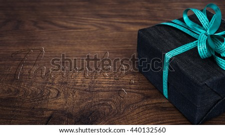 A gift box on wooden board with THANKS water drop text. - stock photo