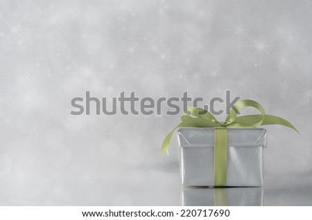 A gift box with closed lid, wrapped in metallic silver paper and tied to a bow with green satin ribbon.  Sparkling, star lit bokeh background. - stock photo