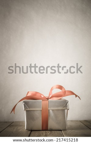 A gift box with closed lid, wrapped in silver paper and tied to a bow with a satin ribbon.  Placed on a weathered old wooden table with copy space behind and above. - stock photo