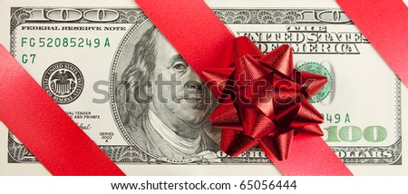 A gift. One hundred bill with red bow and ribbon - stock photo