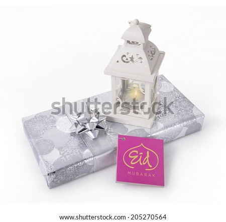 A gift pack with ramadan lamp and tag with 'Eid Mubarak' message - stock photo