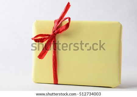 A gift package, very simply wrapped in plain yellow paper with red raffia ribbon tied to a bow.  No label. Copy space on wrapping and background.