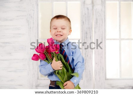 a gift to mum. Adorable little boy with a bouquet of tulips. On March 8, International Women's Day, Mother's Day - stock photo