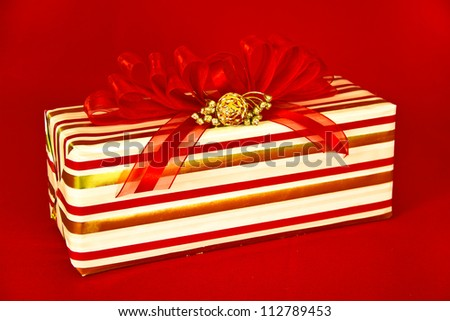 A gift wrapped in red, gold and white striped paper is topped by a red striped bow and gold decorations.