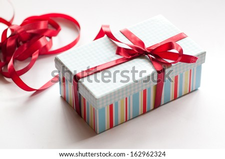 A gift wrapped with red ribbon on a wooden background