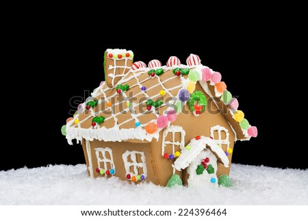 A gingerbread house in snow isolated on a black background can be used as a design element or simply for placement of copy. - stock photo