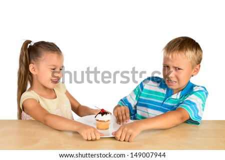 A  girl and a boy are fighting over a single delicious cupcake - stock photo