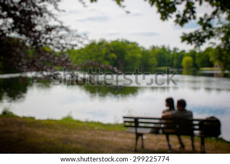 a girl and a man sitting on a Park bench by the lake. The blurred and bokeh background