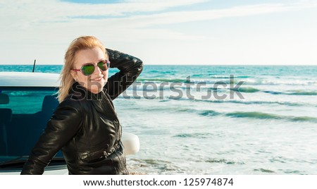 A girl and her car on the seaside - stock photo