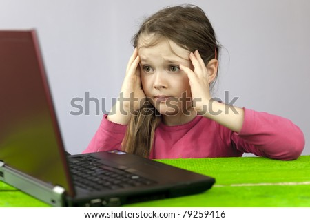 a girl at the laptop, which has difficulty with homework