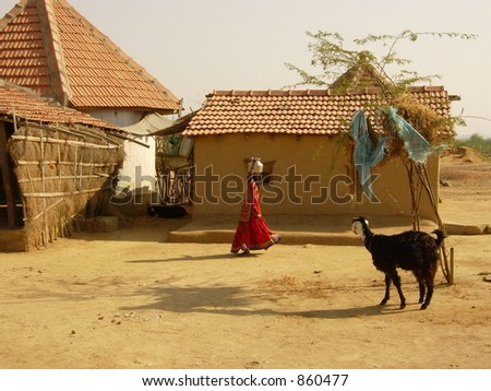 a girl carrying a vessel on her head in a village in india - stock photo