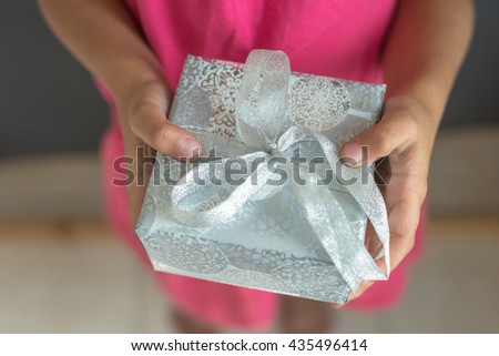 A girl child holding a gift box. - stock photo