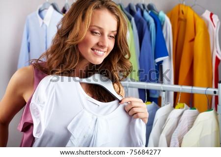 A girl choosing a t-shirt in the shop - stock photo