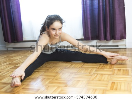 A Girl doing yoga sitting at home with window on the back - stock photo