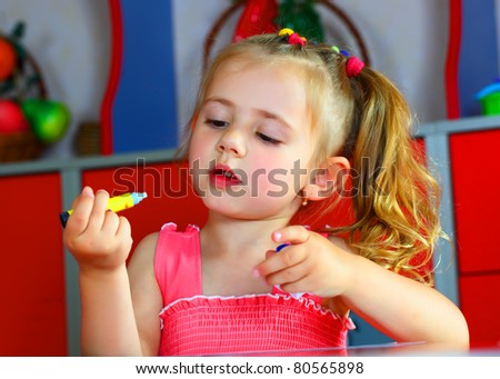 A girl draws with crayons - stock photo